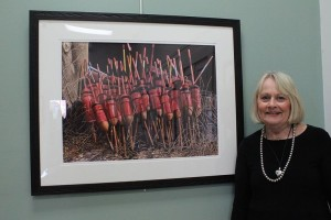 "Jane Stoddard poses with his most recent painting ""Ladies in Red."" The image, which depicts lobster bouys from Maine, took three months to complete and, according to Stoddard, and was one of her most difficult paintings."
